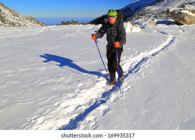 Hiker ascending the trail on snowy mountain