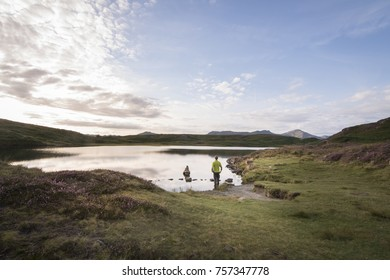 Hiker awing over the beautiful scene with lake district mountain background and purple heather