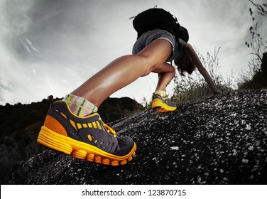 Hiker with backpack climbing rocky terrain. Focus on the boot