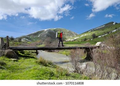 hiker with backpack crossing primitive bridge of wooden trunks on creek in Nebrodi Park, Sicily