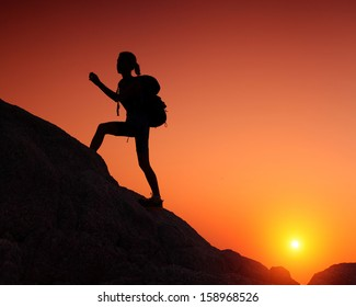 Hiker with backpack crossing rocky terrain