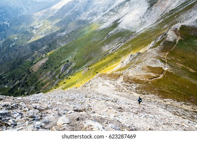 Hiker with backpack in distance on picturesque highland landscape standing on curvy trail over steep mountain, shot from above. Pirin mountain under the peak Vihren, Bulgaria
