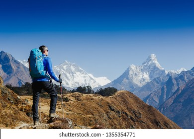 Hiker with backpack enjoying the Ama Dablam mountain view view Everest trek in Himalayas. Success, freedom, active sport concept