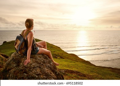 Hiker with backpack enjoying sunset listening to music on peak of mountain. Mountains and sea landscape, travel to Asia, happiness emotion, summer holiday concept
