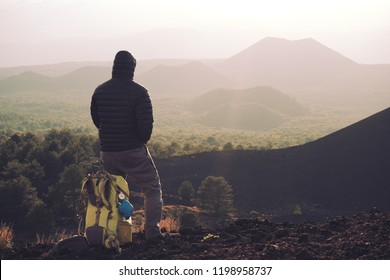 hiker with backpack enjoying sunset on old volcanic cone in Etna Park, Sicily