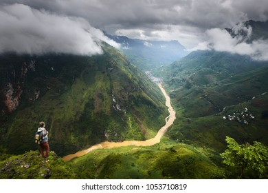 Hiker with backpack enjoying view mountain gorge Ma Pi Leng. Province Ha Giang, North Vietnam.