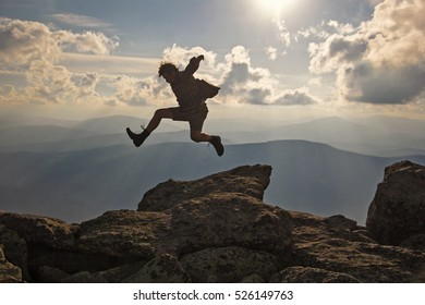 Hiker with backpack jumping over rocks  sunset sky on the background