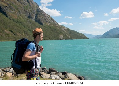 hiker with backpack looking at Gjende lake in Jotunheimen National Park, Norway