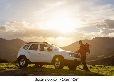 Hiker with backpack looking at a map on the hood of his off-road car at sunset. Traveler and adventurous person traces his mountain route on a map. suv vehicle.