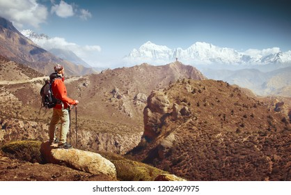 Hiker with backpack looks at beautiful mountains in Upper Mustang, Annapurna conservation area, Trekking route, Himalaya. Beautiful inspirational landscape, trekking and activity.