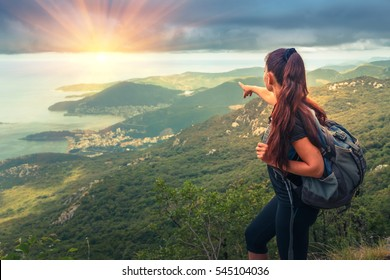 Hiker with backpack  on top of a mountain. Achievement in mountains. Freedom and active life concept.