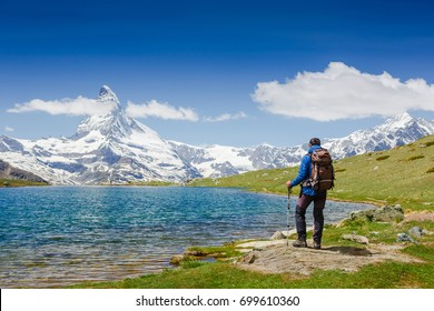 hiker with backpack on the triail near Matterhorn. Swiss Alps