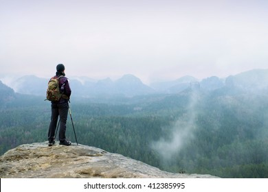 Hiker with backpack and poles on cliff rock  watching over the misty and foggy spring valley to Horizon. Melancholy weather.