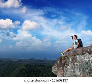 Hiker with backpack relaxing on top of a mountain