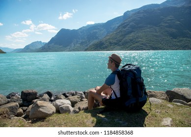 hiker with backpack resting near Gjende lake in Jotunheimen National Park, Norway