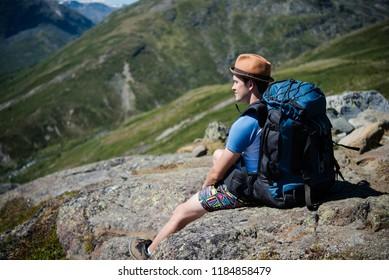 hiker with backpack resting on Besseggen ridge in Jotunheimen National Park, Norway