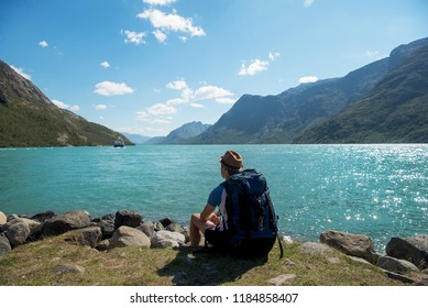 hiker with backpack sitting and looking at Gjende lake in Jotunheimen National Park, Norway