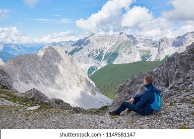Hiker with backpack sitting on top of the mountain and enjoying the valley view at sunny day. Man, Austrian Alps.