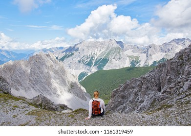 Hiker with backpack sitting on top of the mountain and enjoying the valley view at sunny day. Girl, Austrian Alps.