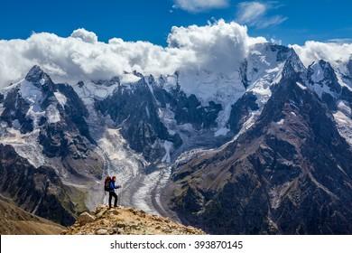 Randonneur avec sac à dos debout en haut de la montagne et profitant de la scène