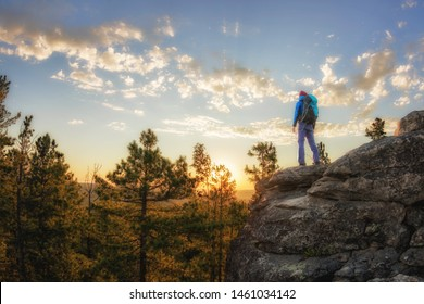 Hiker with backpack standing on a rock and enjoying sunset on mauntain