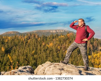Hiker with backpack standing on top of a mountain admiring the view