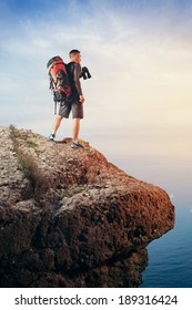Hiker with backpack standing on top of a mountain and looking at the landscape through binoculars