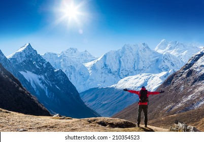 Hiker with backpack standing on top of a mountain and enjoying sun