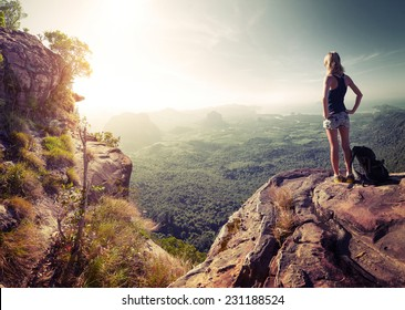 Hiker with backpack standing on top of the mountain and enjoying valley view at sunrise