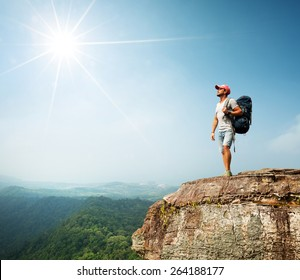 Hiker with backpack standing on top of the mountain