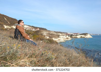 Hiker with backpack standing on top of a mountain and looks into the distance on blue sea