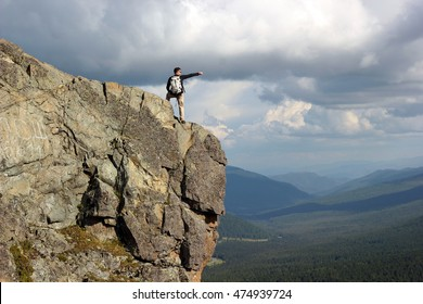 Hiker with backpack standing on top off high rocks. Tourism concept.