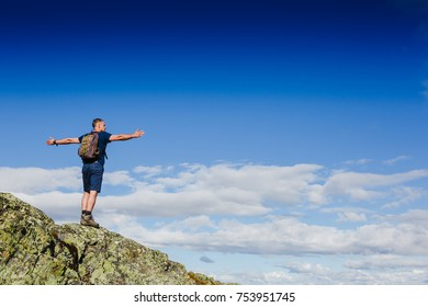 Hiker with backpack standing on top of a mountain and enjoying tne view