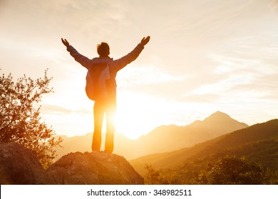Hiker with backpack stands on che rock cliff in the mountains over the rising sun