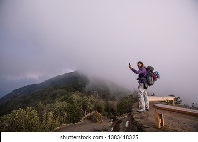 Hiker with backpack staying on mountain top above clouds and jungle valley, doing pictures or try to catch 3g internet on mobile phone