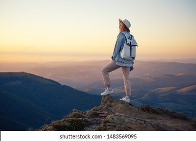 Hiker with backpack in the top of the mountain. Young girl walking in the mountains during sunset. Mountains and people. Adventure and travel - image