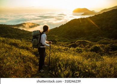 Hiker with backpack and Trekking Pole enjoying sunset on a dense Rain Forest in Brazil