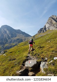 Hiker with backpack walking a grass trail on top of a mountain and enjoying valley view during trip in the alps with sunbeam
