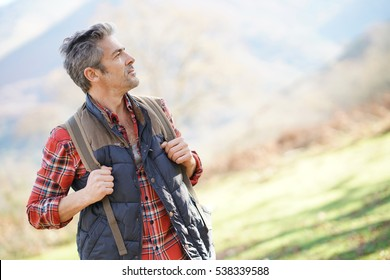 Hiker with backpack walking in the mountain