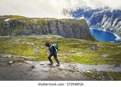 Hiker with backpack walking up to summit in Norway mountains by trail to Trolltunga nature attraction. Fitness and healthy lifestyle outdoors at wild pristine nature background.