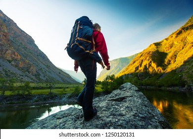 Hiker with backpack walks towards the top of the stone located in the valley with mountains covered by a morning sunrise light. Altai, Russia