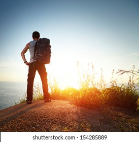 Hiker with backpack watching sunset over sea
