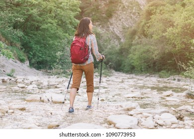 Hiker backpacker young woman with trekking poles walking along the river gorge in summer.