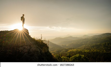 Hiker, Backpacking on top of a mountain cliff. Dreamy Dramatic Sunset Composite. Landscape taken in Lusatian mountains with wide panorama. Concept: Adventure, Art, Travel, Hike, Outdoors and Sports.
