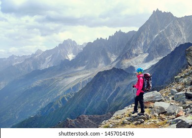 Hiker with backpacks relaxing on top of a mountain and enjoying the view of valley
