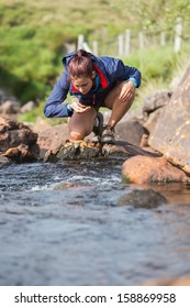Hiker bending to take a drink from the stream in the countryside