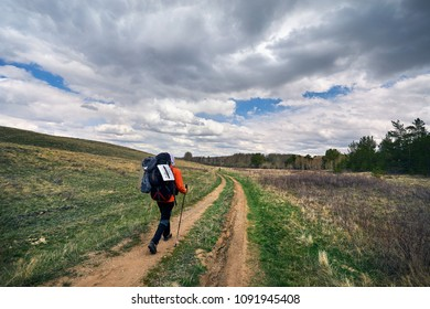 Hiker in with big backpack walking to the country road near the forest against cloudy sky in Karkaraly national park in Central Kazakhstan