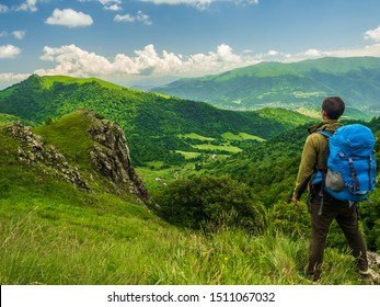 Hiker with big blue backpack is standing among grass on a green rocky hillside, looking into beautiful valley lying below. Summer hiking in Dilijan national park, Armenia.