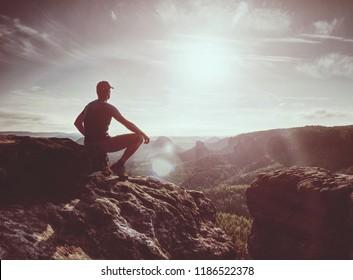 Hiker in black on the rocky peak. Daybreak in mountains, mist in deep valley. Man sit on the rock.