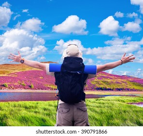 Hiker with black rucksack spreads hands expressing happiness on beautiful Scottish nature background.